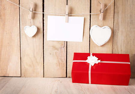 red gift box in front of a wooden wall with hearts and blank paper hanged with pegs photo