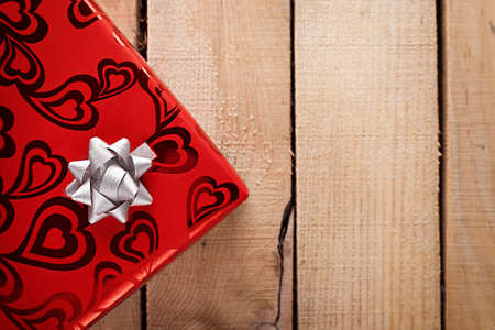 red present with wihte ribbon on wooden background Stock Photo - 19602032