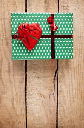 dar un regalo: caja de regalo verde con un corazón rojo sobre fondo de madera