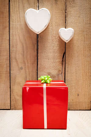 red gift package in front of a wooden wall with two heart hanged photo