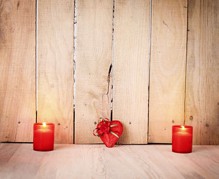 candle light: two candles and a wrapped heart shaped gift on wooden background