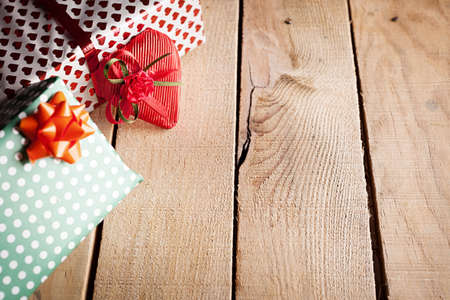 presents and a wrapped heart on wooden background photo