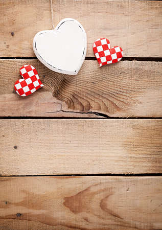 one big and two small hearts on wooden surface  photo