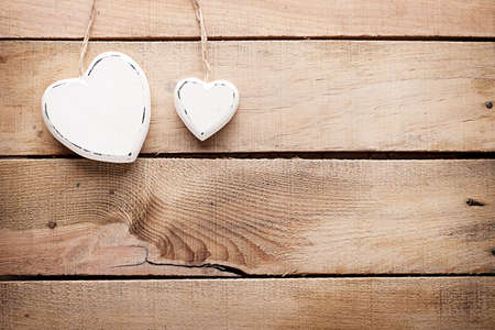 two different sized wooden hearts on wooden background photo