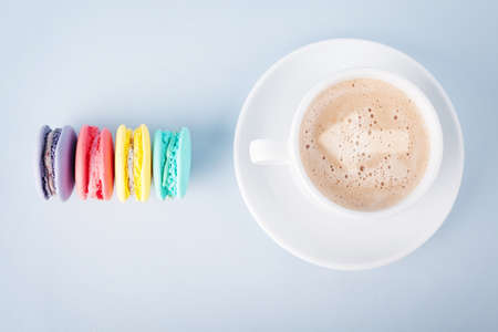 coffee with an arrow sign and colorful macaroons on blue background