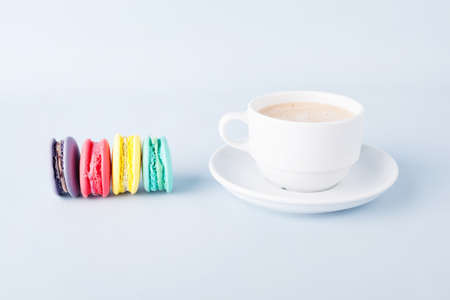 cup of coffee and colorful macaroons on blue background photo
