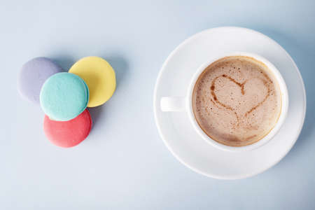 colorful macaroons and a coffee wtih a foam heart on blue background photo