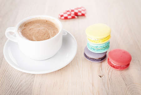 colorful macaroons,hearts and a cup of coffee on wooden table
