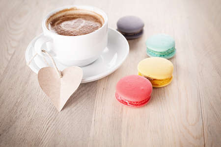 colorful macaroons and a cup of coffee with aheart shaped blank paper on wooden table photo