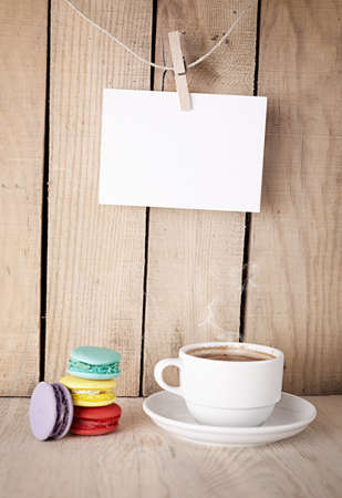cup of coffee, colorful macaroons and a blank note paper on wooden background photo