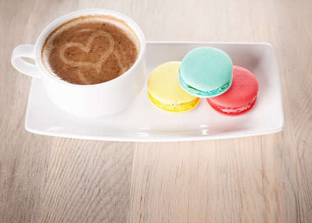 cup of coffee and colorful macaroons on a porcelain plate on wooden table photo