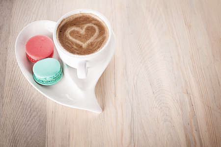 cup of coffee and macaroons in a heart shaped porcelain on wooden table