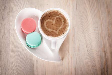 マカロン: コーヒーのカップと木製のテーブルにハート形の磁器のマカロン