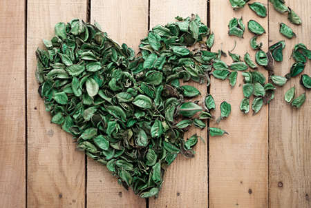 heart made of leaves fading away on wooden background photo
