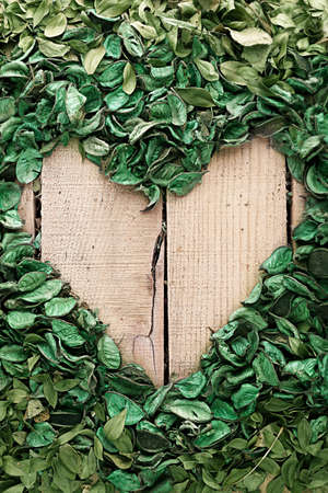 vertical heart frame made of leaves on wooden background photo
