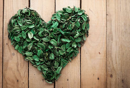 heart shape made of leaves on wooden background with copyspace photo