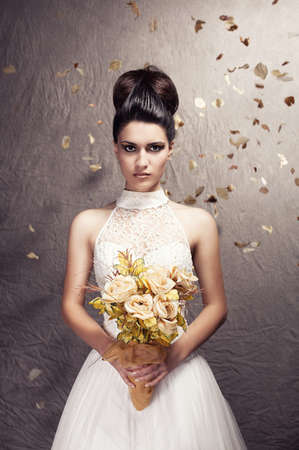 beautiful young woman wearing a wedding dress posing on grunge background photo
