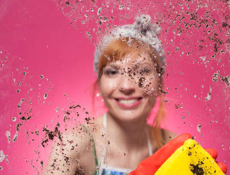 young lady cleaning the glass with a yellow cleaning towel on pink background photo