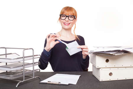 business woman sitting her desk getting rid of old papers photo