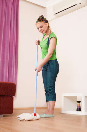 house maid: beautiful young lady wearing casual clothes, mopping the floor