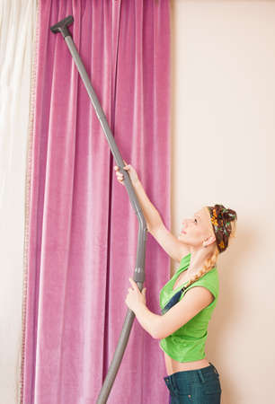 home keeping: beautiful young lady using a vacuum cleaner for hoovering the curtains