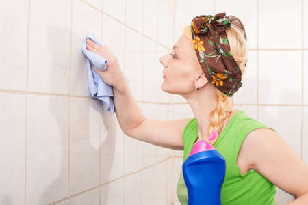 hairband: young lady with hairband cleaning the tiles with a cleaning towel Stock Photo