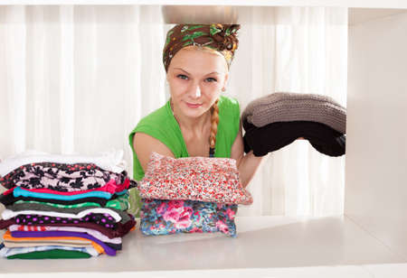 young lady removing her winterweight clothes in order to put her spring clothes in her wardrop photo