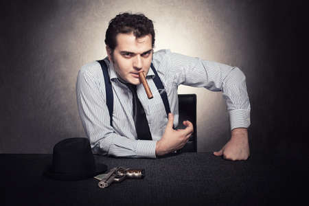 the godfather: serious gangster sitting and looking at camera on grunge background Stock Photo