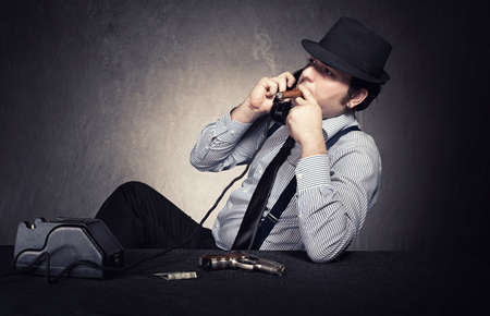 old fashioned gangster having a conversation on phone on grunge background photo