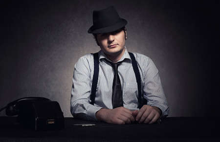 the godfather: calm godfather with black hat looking at camera on grunge background Stock Photo