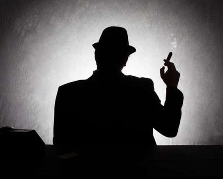 gangster background: silhouette of retro style gangster holding his cigar on grunge background
