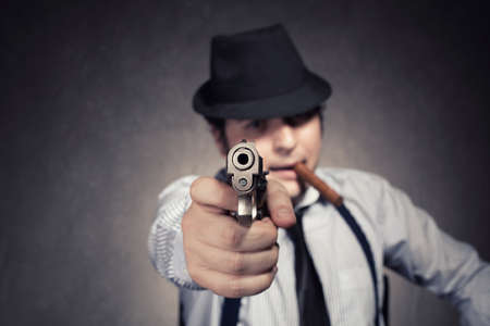 gangster with a gun threatening you on grunge background with shallow depth of field with gun in focus photo