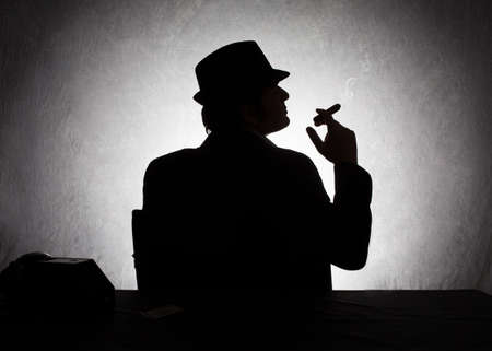 spies: silhouette of retro style gangster holding his cigar on grunge background