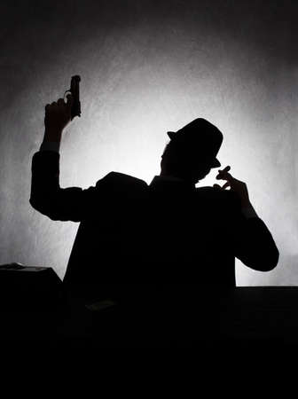 secrets: silhouette of retro style gangster holding his gun on grunge background