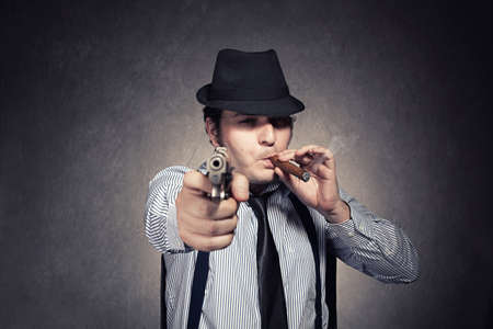 young gangster holding a gun threats you on grunge background.gangster is in focus photo