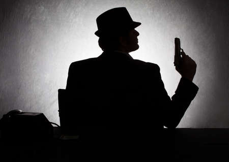mystery man: silhouette of retro style gangster holding his gun on grunge background