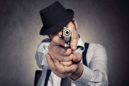 vintage gun: retro ganster wants to shoot you with his gun on grunge background with shallow depth of field with the gun in focus