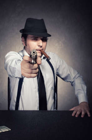 retro gangster with a gun wants you dead on grunge background.shallow depth of field with the gun in focus photo
