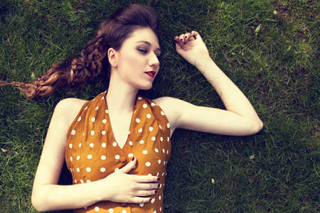 portrait of a young beautiful woman laying on green grass photo