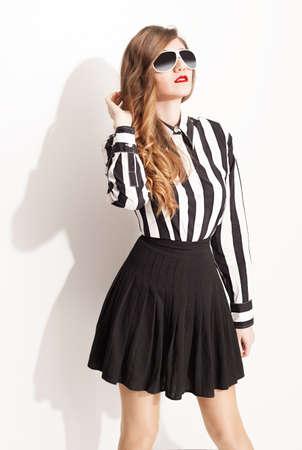 falda: modelo de moda joven con gafas de sol y posando falda plisada en el fondo blanco