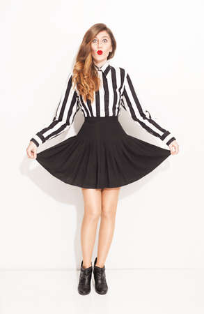 amused: young lady with lined black and white shirt and pleared black skirt posing on white background