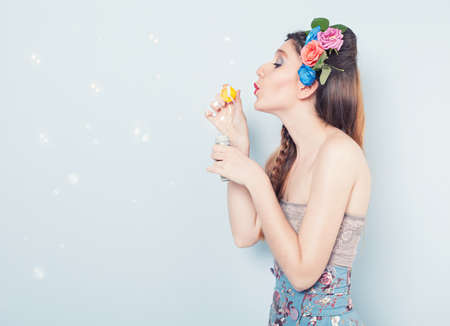 profile of a young beautiful lady blowing soap bubbles on blue background photo