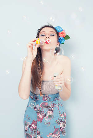 young lady with a circlet made of flowers blowing soap bubbles on blue background photo