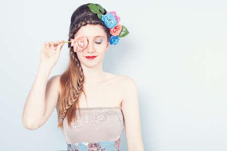 mujer pirata: joven y bella modelo que sostiene una rosa rosa en frente de su ojo derecho y cerrando su otro ojo en el fondo azul Foto de archivo