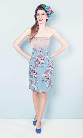 circlet: giovane donna con il vestito blu e un cerchietto di fiori sorridendo e guardando la telecamera su sfondo blu