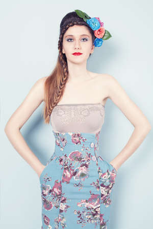 braided hair: portrait of young fashion model with a blue spring dress and a circlet on her head on blue background