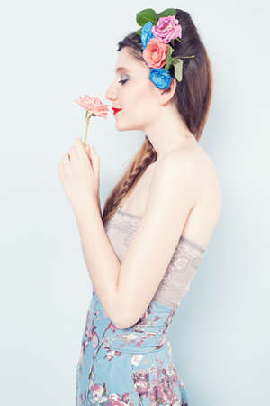 braided hair: profile portrait of a young lady smelling a pink rose on blue background