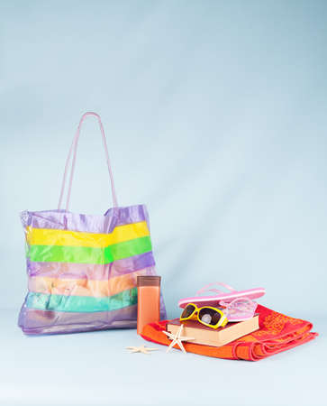 summer conceopt with beach bag and various summer stuff on blue background photo