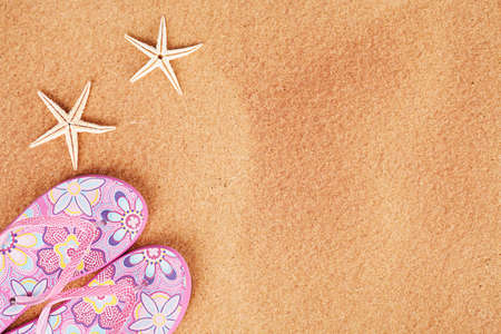 seasonal concept with two starfishes and sandals on sand photo