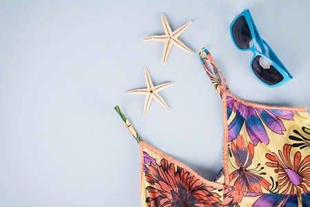 summer dress and sunglasses with two star fishes on blue background photo